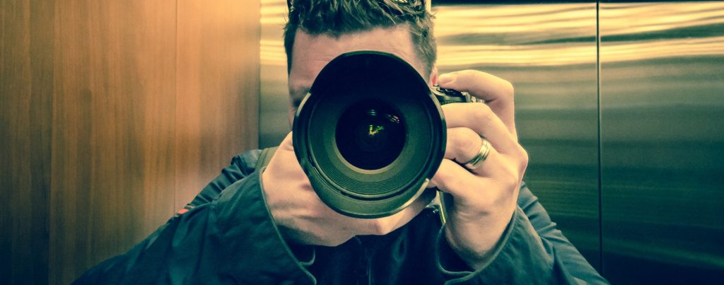 Man holding camera up to his face to take a photograph