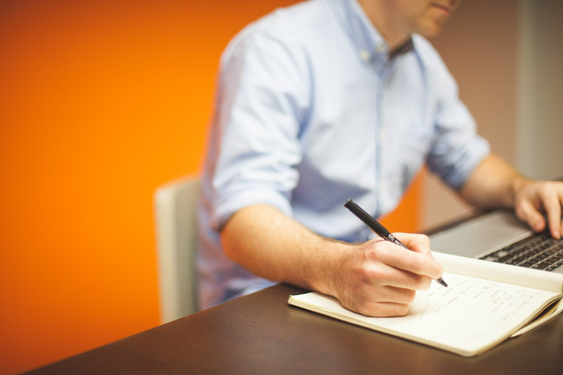Man in blue button down writing in notebook against orange wall