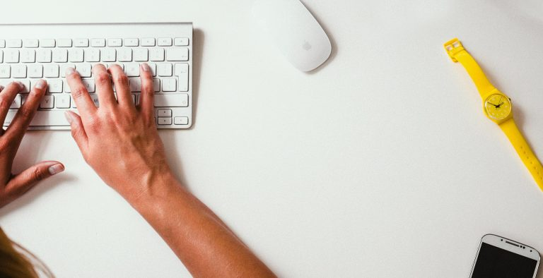 Hands typing on white keyboard with yellow watch nearby