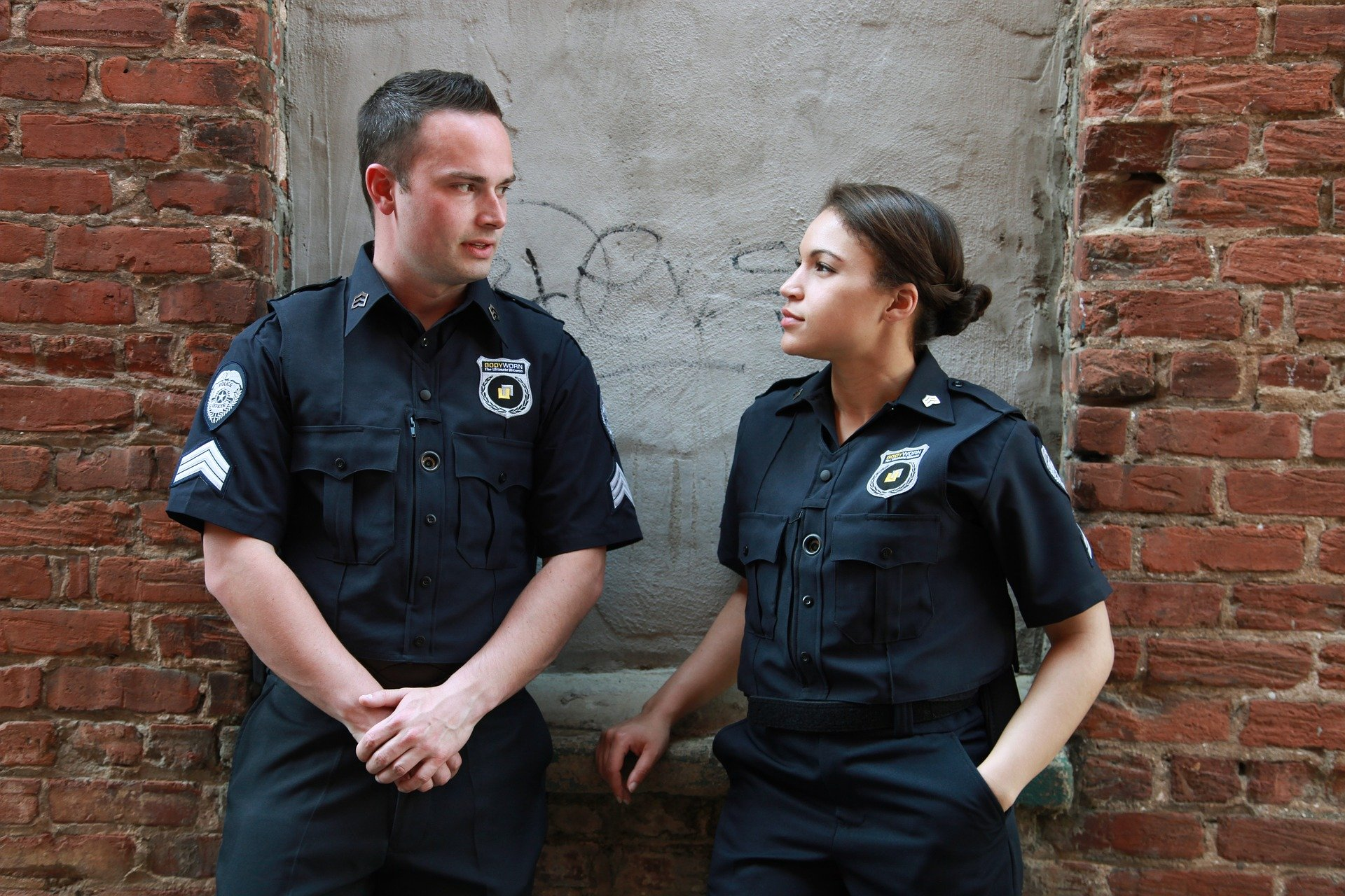 Man and woman police offers talking in front of concrete and brick wall