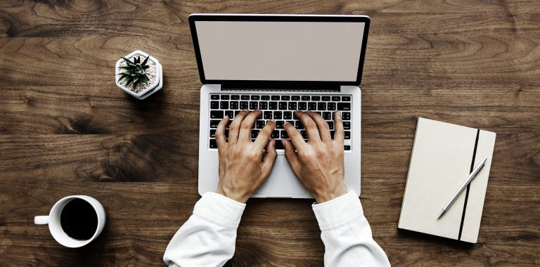 Overhead shot of man's hands typing on laptop with coffee and notebook nearby on wooden table