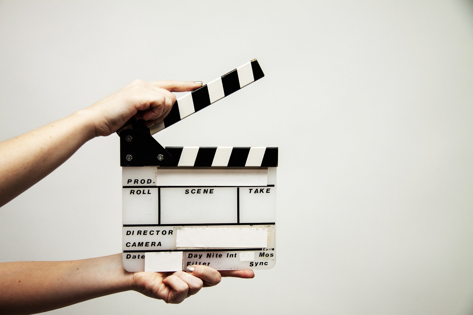 Two hands holding a video clapperboard against a white wall